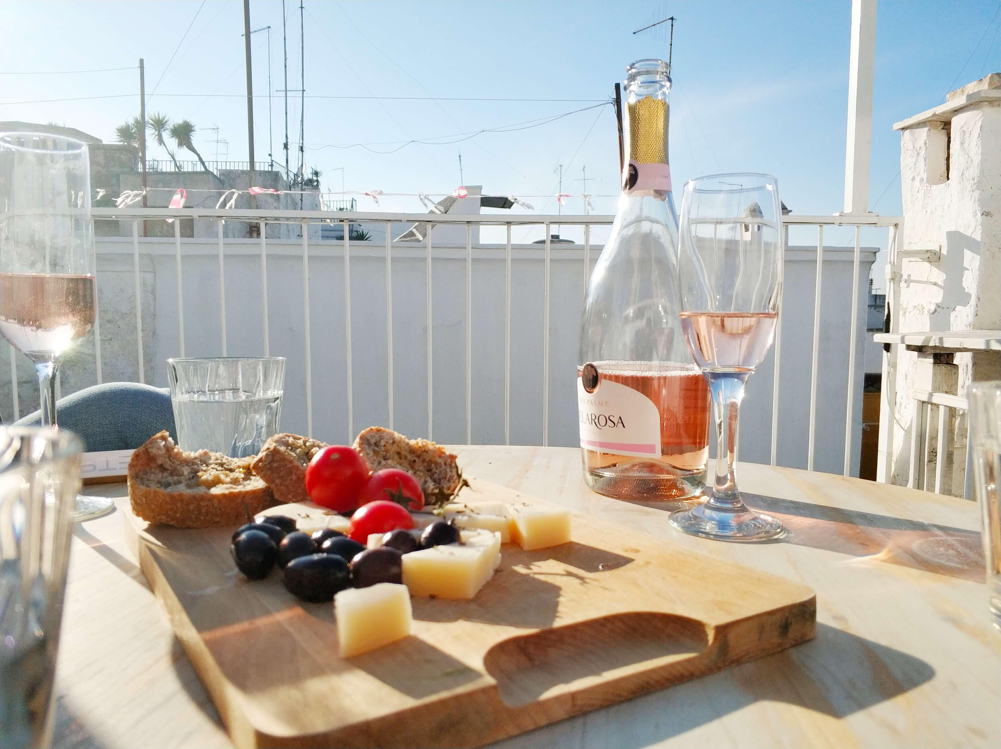 Плато със сирена, маслини и чери домати и бутилка роза на покрив в град Остуни